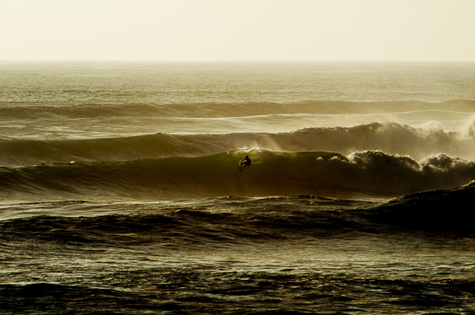 The unknown surfer, zipping across the waves like a masked creature of the darkness with the night vision of an owl.