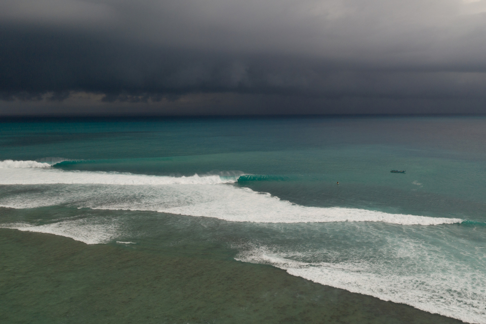 An eerie beauty. No one here, firing waves, sinister sky.